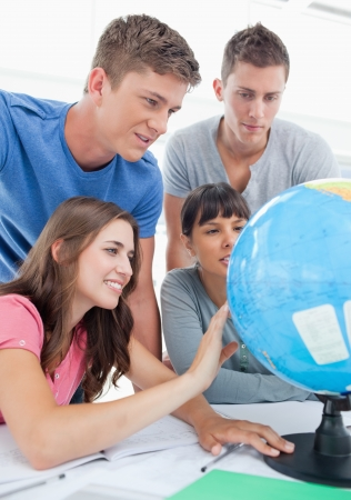 A close up shot of four people sitting in front of the globe and looking for a place