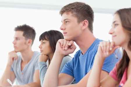 A side view of a group of students thinking with hands on their chins Stock Photo - 16237303