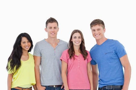 Four people standing beside each other and smiling while they all look at the camera