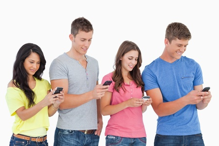 A group of four friends standing slightly to the side as they all send texts on their phones  photo