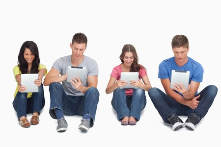 women in jeans: A group of four people sitting beside each other on the ground as they all use their tablet pcs