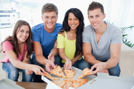 eating pizza: A smiling group of people taking a slice of pizza as they look into the camera