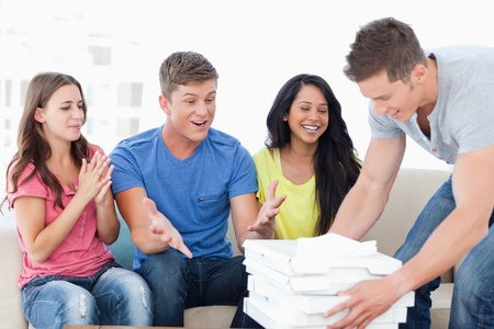 A group of friends celebrate as a man brings them some pizza photo