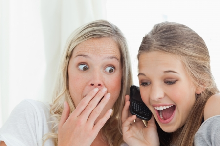 A pair of surprised and smiling sisters listening to a phone call photo