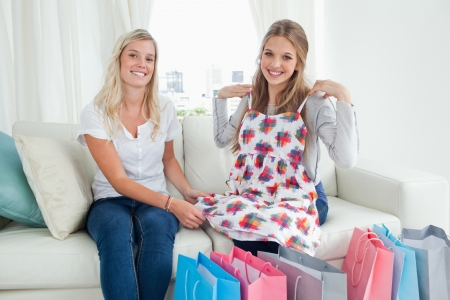 A pair of smiling girls trying on new clothes while on the couch as they look at the camera  Stock Photo - 16237248