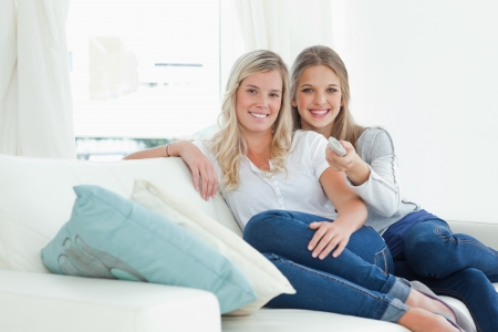 A pair of sisters looking at the camera as they laugh with a tv remote  Stock Photo - 16235120