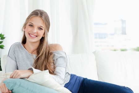 A smiling girl lying on the couch as she looks at the camera Stock Photo - 16235103