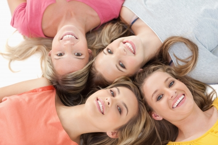 girl lying: Four smiling girls lying on the ground together with their heads beside one another Stock Photo