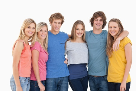 A group of friends smiling and holding each other while looking at the camera