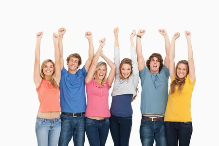 A smiling group of friends with their hands in the air as they look at the camera Stock Photo - 16234887