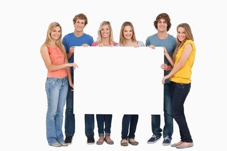 hoja en blanco: Un grupo de amigos que sostiene la hoja en blanco