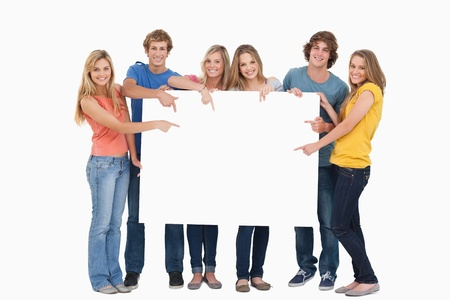 Smiling group of people with a blank space as they point to it and look at the camera Stock Photo - 16233797
