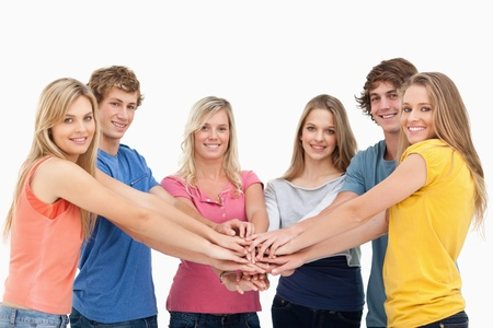 Friends standing around each other as they stack their hands while they look at the camera Stock Photo - 16235519
