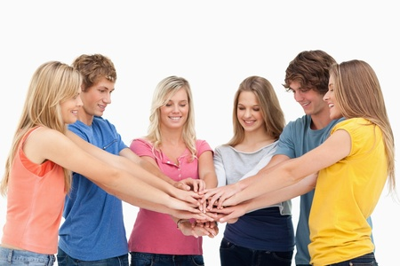 A group of friends with their hands stacked on top of each other as they look at the stack Stock Photo - 16236278