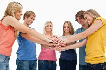 Low angle shot of friends smiling and looking at their hands stacked in the centre Stock Photo - 16237989