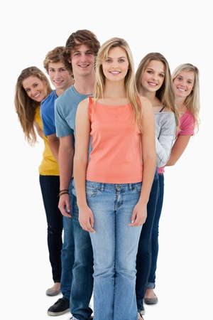 A full length shot of a smiling group standing behind one another at various angles while lookinng into the camera Stock Photo - 16236351