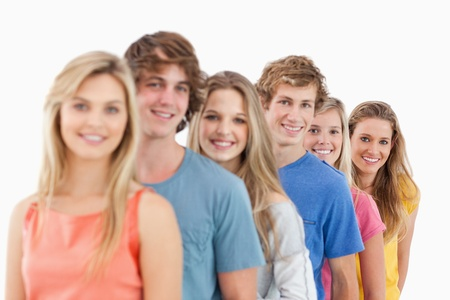 A smiling group standing behind each other at an angle while looking at the camera Stock Photo - 16236360