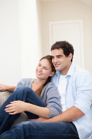 Couple sitting while embracing each other indoors photo