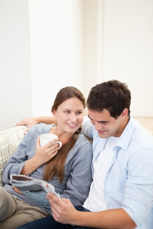 Couple sitting on a sofa while reading a newspaper in a sitting room photo