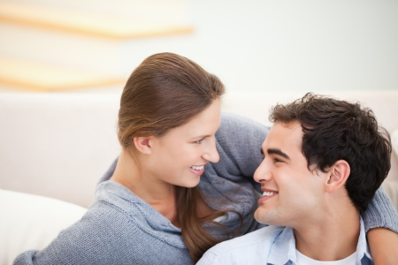 Couple looking each other while embracing in a sitting room Stock Photo