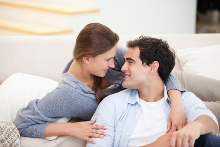 Couple embracing eachother while sitting a sofa in a sitting room photo