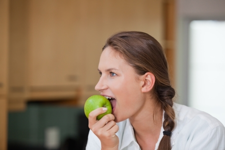 Woman eating an apple in a kitchen  photo