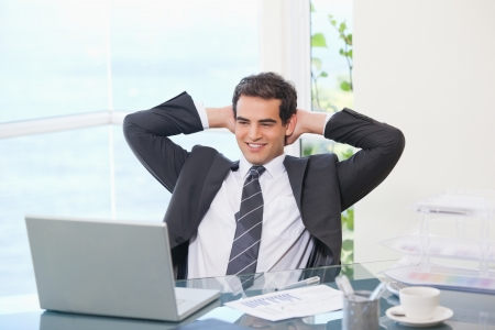 Man crossing his arms behind his head  in an office photo