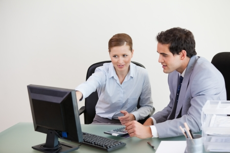 Colleagues working together on a computer against grey background photo