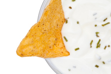 nacho: A nacho dipped into a bowl of white dip with herbs against a white background