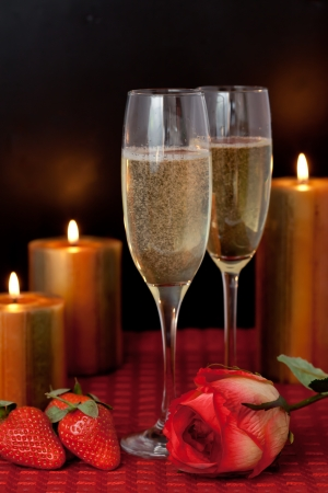 Glasses of champagne with strawberries and a rose beside candles on a red tablecloth against a black background Stock Photo - 16234931