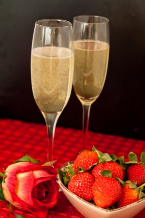 Top glasses of champagne with strawberries in a bowl and a rose on a red tablecloth against a black background photo