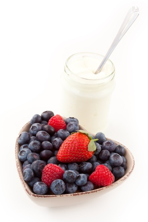 Berries in a heart shaped bowl with yogurt against a white background photo