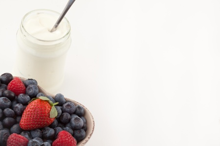 Berries in a heart shaped bowl with white yogurt against a white background photo