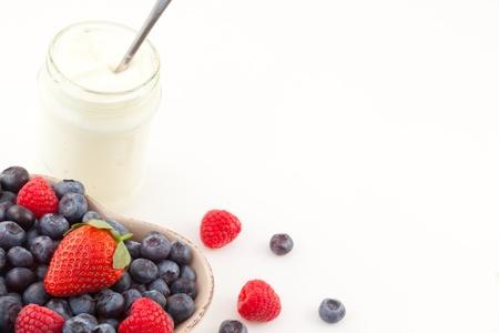 Yogurt and berries against a white background photo