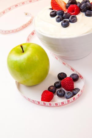 Apple and bowl of berries cream and  a tape measure against a white background photo
