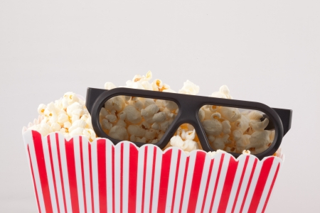 3D glasses on top of a box of popcorn against white background photo