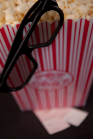 Glasses hanging on the edge of a box of pop corn standing on two tickets Stock Photo - 16206862