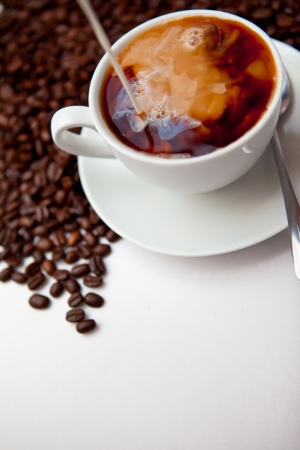 Black coffee and milk  with beans against a white background photo