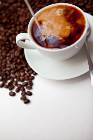 Schwarzer Kaffee und Milch mit Bohnen vor einem weißen Hintergrund