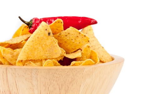 Pepper upon a bowl full of crisps against white background photo