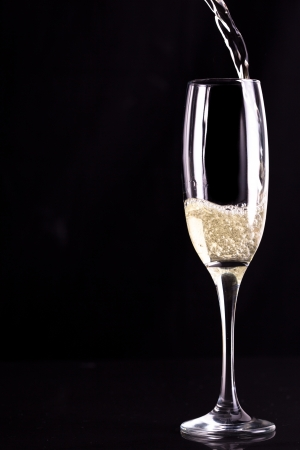 celebration champagne: Glass of champaigne being filled against black background Stock Photo