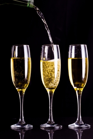 Two full glasses of champagne and one being filled against black background photo