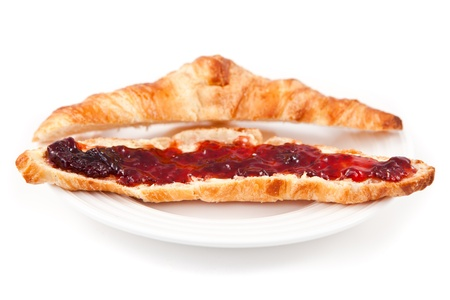 plateful: Croissant spread with jam in a plateful against white background