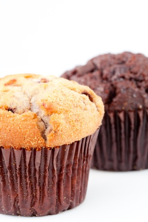 Close up of two fresh baked muffin and a blurred chocolate muffin against a white background Stock Photo - 16207916