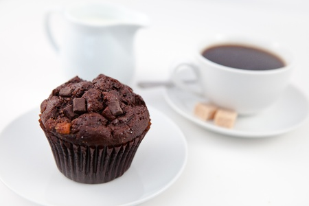 Chocolate muffin and a cup of coffee on white plates with sugar and milk against a white background photo