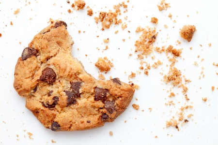 chocolate chip cookies: Close up of an half eaten cookie with crumb against a white background