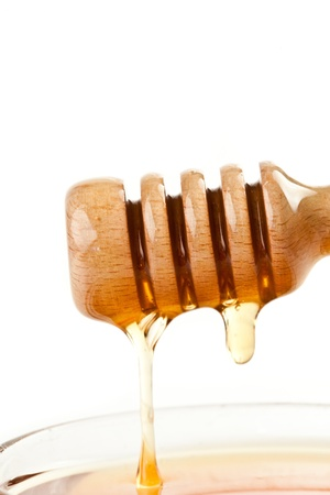 Honey trickle on the top of a honey full bowl against a white background Stock Photo - 16202190