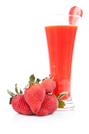 Strawberries in front of a full glass against white background photo