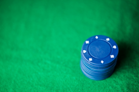 Blue poker chips on the green mat Stock Photo - 16202076