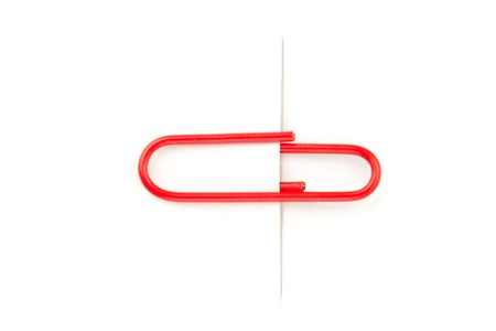 attaching: Close up of a red paperclip attaching on a white paper against a white background